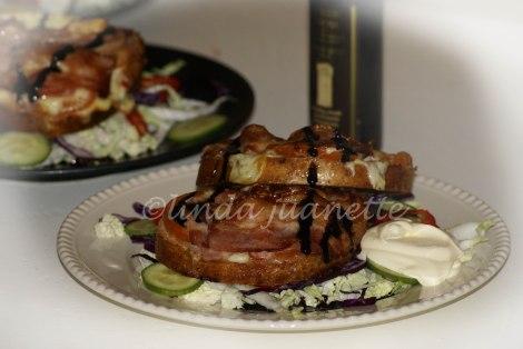 Legg smørbrødene oppå salaten og ha balsamicoeddik over.