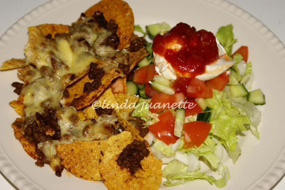 Sprø nachos med tacokjøtt og smelta ost smaker veldig godt sammen med salat, rømme og salsa.
