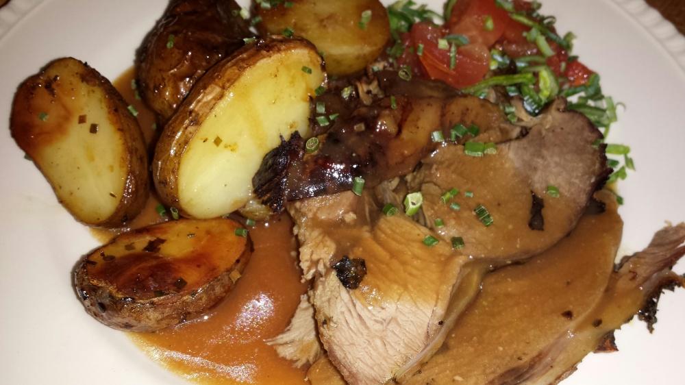Langtidsstekt lammelår med urter, ovnsbakte poteter og sjysaus.