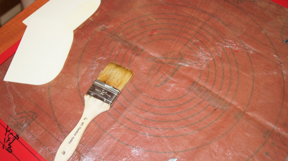 Forberedelser før du går i gang med å koke dropsmassen: Legg en håndduk under teflonmatten og smør den med smeltet smør. Smør også deigskrapene og saksen som skal brukes til å klippe dropsene.