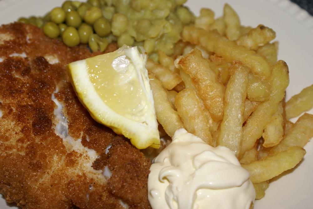 Fish&Chips servert med hele hermetiske erter og erterstuing, sitron og dressing.
