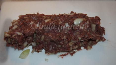 Legg kjøttdeigen på matpapir/bakepapir og form den til en avlang rull.