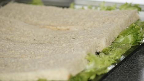 Bruk et stor serveringsfat til å lage terten på og start med å legge salatblader på brettet, deretter legges underdelen av loffene oppå, tett i tett.