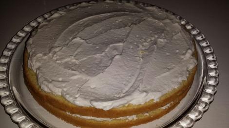 Legg det midterste laget oppå det underste og dynk med sukkerlake, og smør over et tynt lag med pisket kremfløte.
