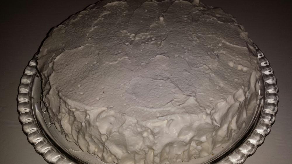Legg toppen  på kaken øverst og dynk med sukkerlake. Smør deretter et lag pisket kremfløte langs sidene og et tynt lag på toppen.