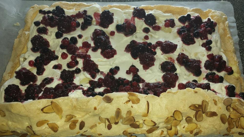 Ha pisket kremfløte med hakkede bananer utover kaken. Legg bær jevnt over hele og rull sammen så stramt som det er mulig.