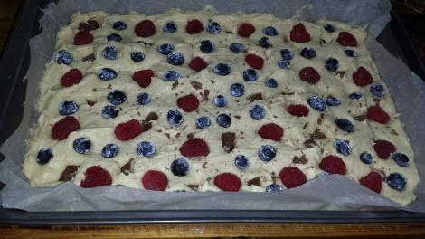 Legg sjokolade, bringebær og blåbær på kakedeigen. Man trenger ikke dytte det ned i deigen.